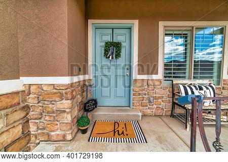 Blue Front Door With Wreath And Old Bench Against Window At The House Facade