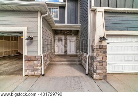 Townhouses With Side By Side Front Doors And Steps Between Attached Garages