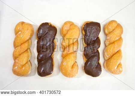 Top View Flat Lay Of Row Of Alternating Glazed Twist Donut And Chocolate Covered Glazed Twist On Par
