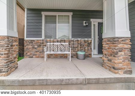 Home Facade With White Bench On Porch Against Gray Siding And Stone Brick Wall
