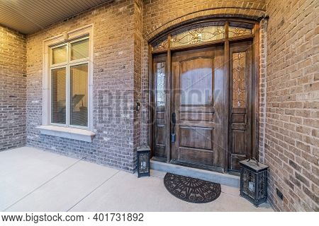 Beautiful Facade Of House With Front Door And Window Against Stone Brick Wall