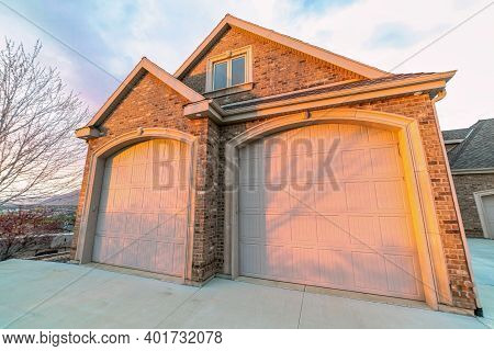 Gable Roof Garage With Two Arched Doors And Brick Wall Against Cloudy Sky