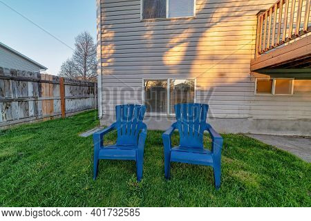 Blue Chairs On Grass Lawn At The Backyard Of Home With Deck And Wall Siding