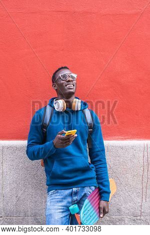 Black Man Holding Skateboard Using Cellphone Wearing Blue Sweater Outdoors.