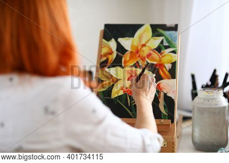 Close-up Of Talented Female Creating New Picture Of Flowers. Creative Red Haired Painter Sitting In