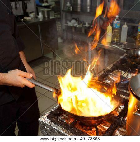Chef is making flambe dish on restaurant kitchen