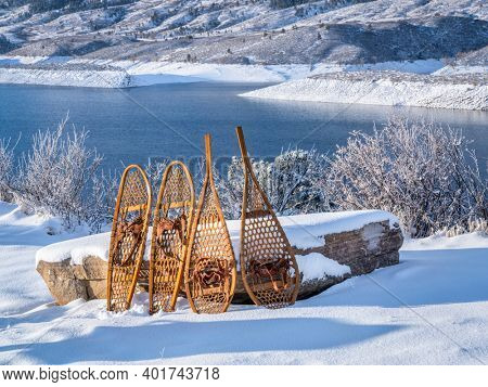 classic wooden snowshoes in winter scenery of a moun tain lake - Horsetooth Reservoir in northern Colorado