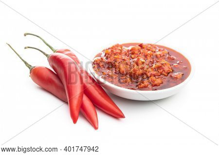 Red hot chili paste in bowl and chili peppers  isolated on white background.