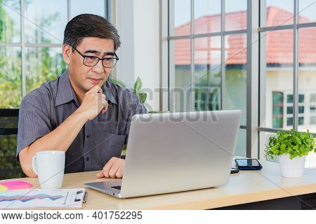 Asian Senior Business Man Working Online On A Modern Laptop Computer He Looking At The Screen For Re