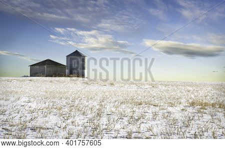 An Empty Grain Silo And Shed Sit On A Harvested Snow Covered Field On The Canadian Prairies In Rocky