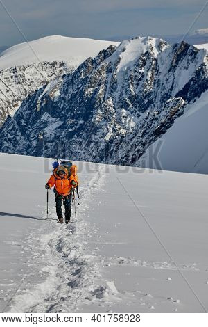 Two climbers walking on glacier with crevasse