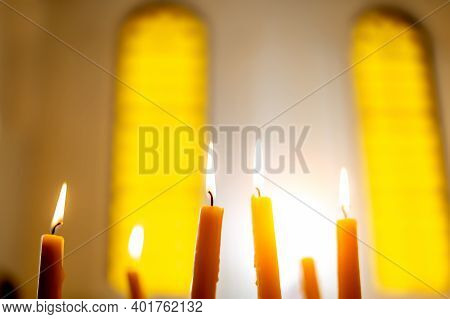 Burning Candles In The Church On A Blurry Background.