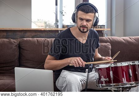 A Man Plays The Drum And Looks At The Laptop Screen. The Concept Of Online Music Lessons, Video Conf
