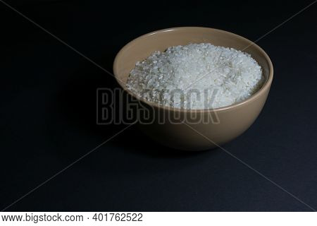 White Uncooked Rice In A Bowl With Scattered Grains Nearby On A Black Background