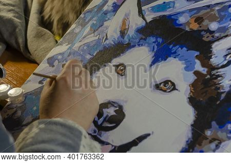 Woman's Brush Hand Paints Colorful Painting Of Husky Dog On Canvas. Process Of Painting Portrait Of