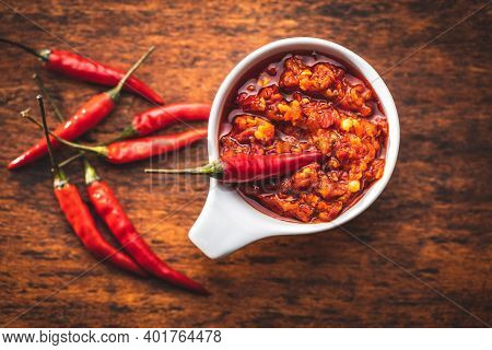 Red hot chili paste and chili pepper in bowl on wooden table. Top view.