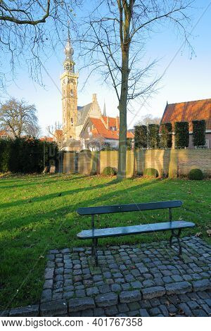 A Bench Along A Paved Street (kerkstaat) With The Stadhuis (town Hall) And Its Impressive Clock Towe
