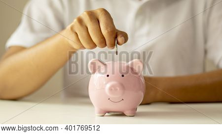 Women Put Money Coins In A Piggy Piggy Bank To Save Money And Save Money For Future Financial And Mo
