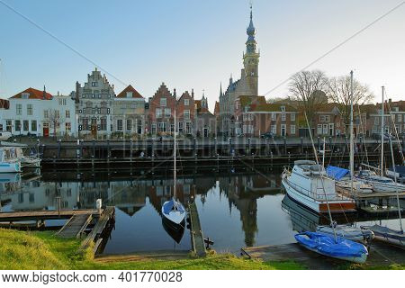 The Marina (harbor) And Historic Buildings With The Clock Tower Of The Stadhuis (town Hall) In Veere