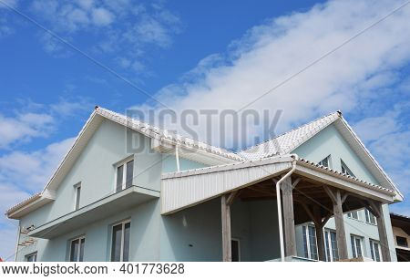 A Light Blue House With Stucco Walls, White Cross Gabled Metal Roof, Rain Gutter System, And A Cover