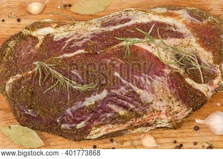 Pickled Piece Of Pork Neck In Spices Prepared For Further Dry-curing On A Wooden Cutting Board, Semi