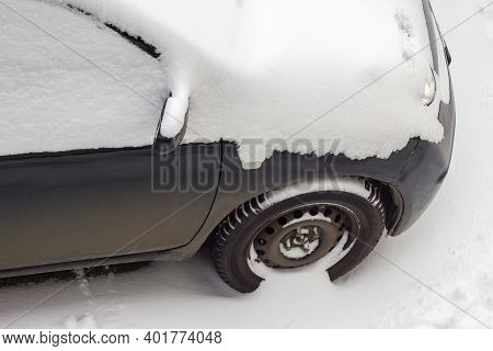 Fragment Of The Front Part Of Black Car Covered With Newly-fallen Fluffy Snow In Cloudy Weather