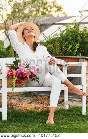 Happy And Healthy Gardener Woman Resting On Bench With Basket Full Of Colorful Flowers, Hobby And Le
