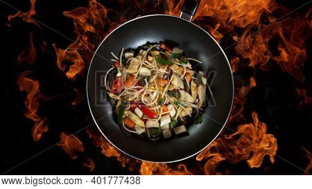 Asian noodles in wok pan, flames on background. High angle view of meat preparation, studio shot.