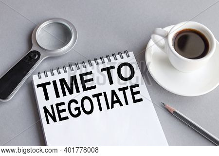 Time To Negotiate, Text On White Notepad Paper On Gray Background. Business Concept. View From Above