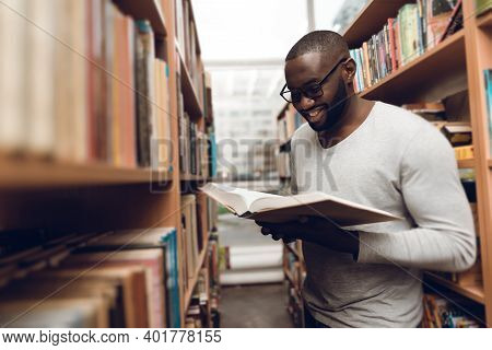 Ethnic African American Guy Reading Book, Smiling In Aisle Of Library.