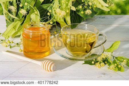 Jar Of Linden Honey, Cup Of Linden Tea And Branch With Linden Flowers On Wooden Table On A Sunny Day