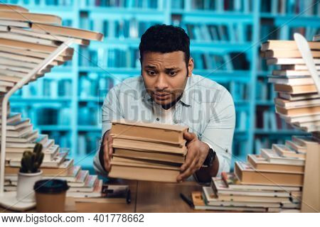 Ethnic Indian Mixed Race Guy Surrounded By Books In Library. Student Is Holding Books.