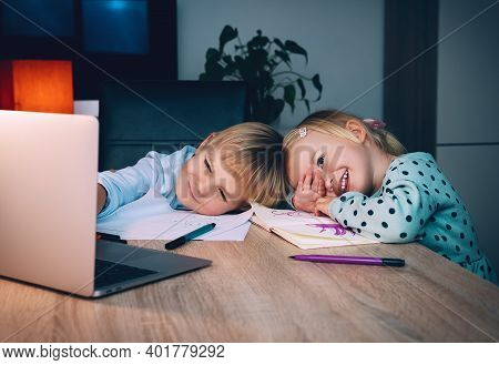 School Boy And Preschool Girl With Laptop At Table In Evening At Home.