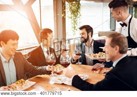 Meeting With Chinese Businessmen In Suits In Restaurant. Business People Sitting At The Table And Di