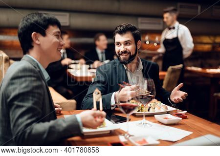 Man Shows Business Partner Charts In A Restaurant. Meeting Of Businessmen In A Restaurant At A Table