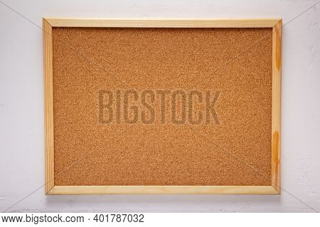 cork board or corkboard at white concrete or putty  wall background texture surface