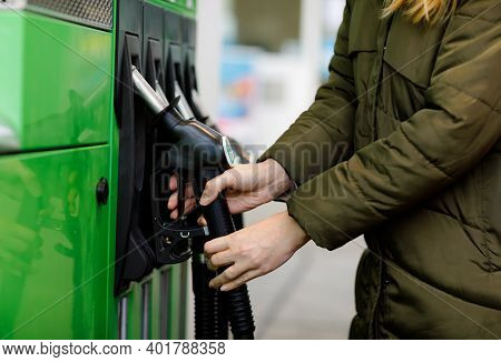 Close-up Of Hands Of Woman At Self-service Gas Station, Hold Fuel Nozzle And Refuel The Car With Pet