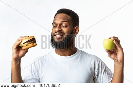 Healthy Vs Unhealthy Food. Hungry African Man Choosing Between Burger And Apple Standing In Studio O