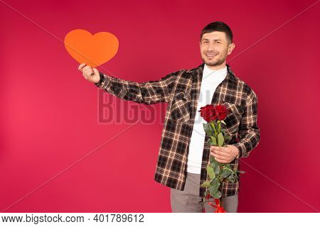 Young Man With A Bouquet Of Roses And With A Red Heart With Empty Space On A Red Background. St Vale