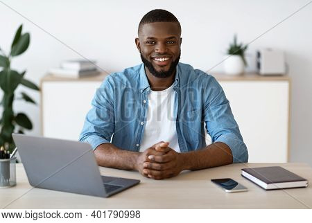 Portrait Of Young Black Freelancer Guy Sitting At Desk With Laptop Computer At Home Office, Looking