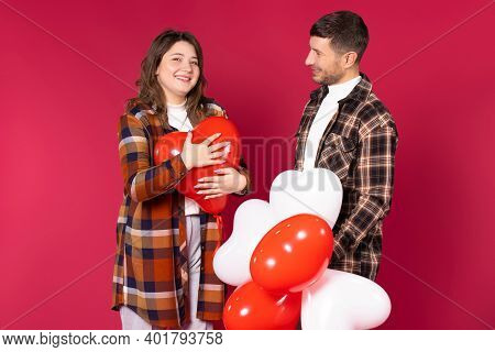 Cute Couple With Red Heart Balloons Smiling And Posing On A Red Background. St Valentine's Day.