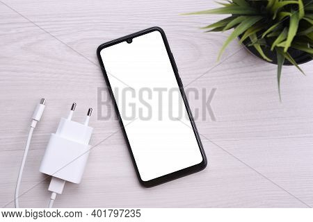 Mobile Phone Smartphone With White Screen For Your Text, Image On A Bright Defective Table With Char
