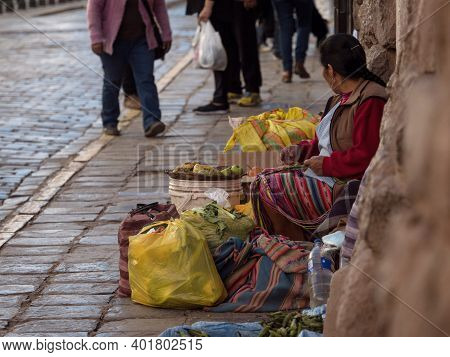 Indigenous Quechua Woman In Traditional Colorful Handwoven Dress Costume Selling Fruits Vegetables I