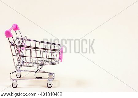 Pink Empty Shopping Cart From The Supermarket As A Symbol Of Consumption And Consumerism On Light Ba