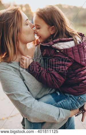 Careful Mother Kissing Her Daughter And Holding Her Outside In A Sunny Day