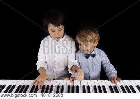 Two Young Boys Of Three And Nine Years Old Are Playing Piano On Isolated Black Background. Well Dres