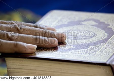 The Hands Of People Who Have Faith Placed On The Books Of Islam. Muslims Believe In The Prophet And