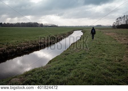 Lonely Hiker In A Wintry Dutch Landscape With Grasslands, Ditches And Threatening Dark Skies