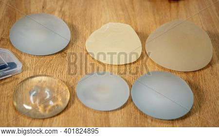 Different Silicone Breast Implants On Table. Demonstration Of Silicone Brest Implants To The Client.