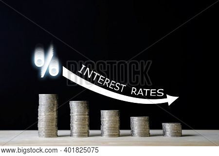 Stacked Us Quarter Coins On Wooden Table With White Illustration Shows Decreasing Of Interest Rates